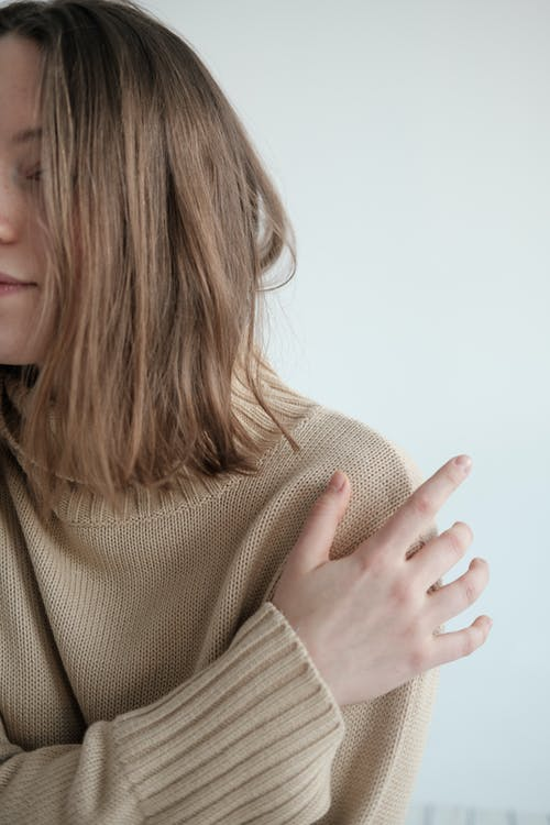 Crop young serene female wearing warm sweater gently touching arm against white background