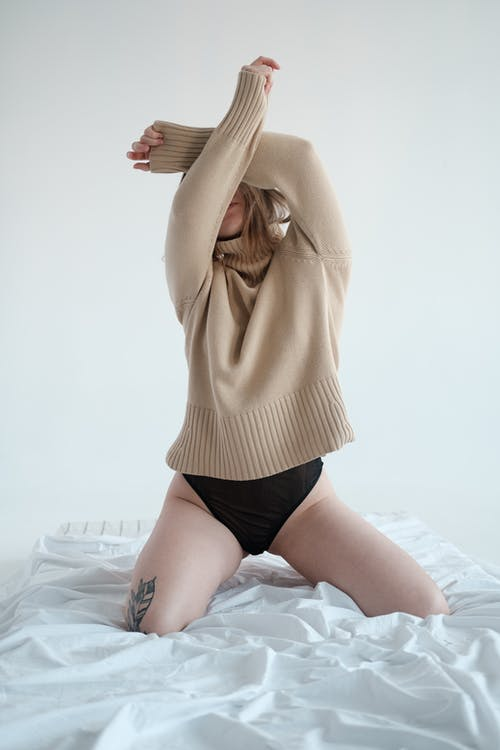 Young unrecognizable female in panties and sweater kneeling on crumpled bed and covering face with raised arms