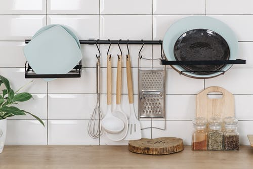 Plates and Utensils on White Wall and Spices on Wooden Surface