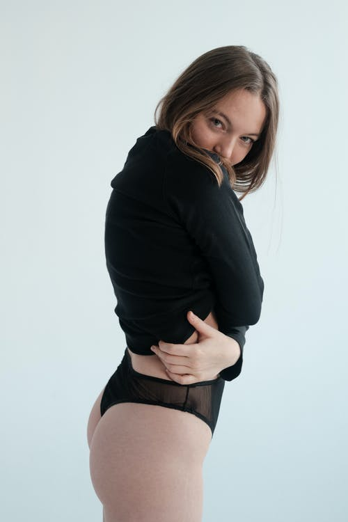 Side view of delicate woman in black underwear and long sleeve standing against white background and looking at camera