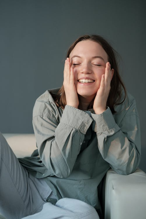 Smiling woman sitting on sofa and gently embracing cheeks