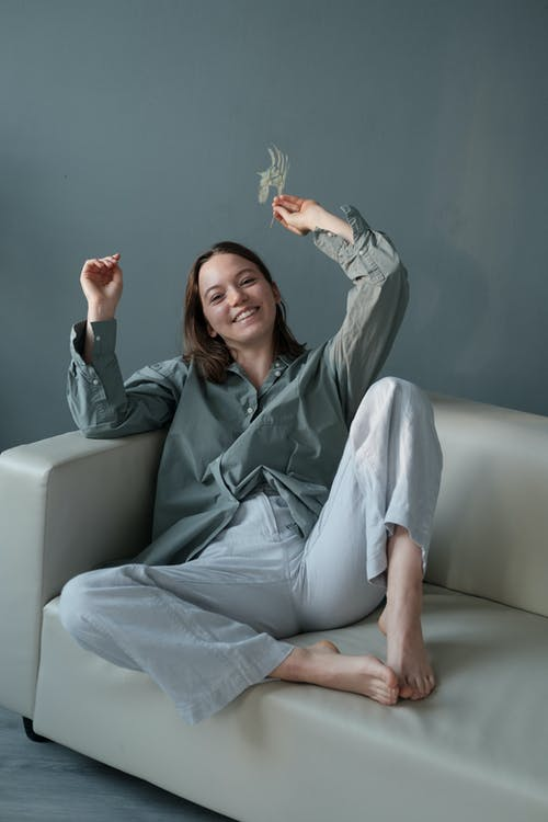 Cheerful woman with branch of plant sitting on sofa