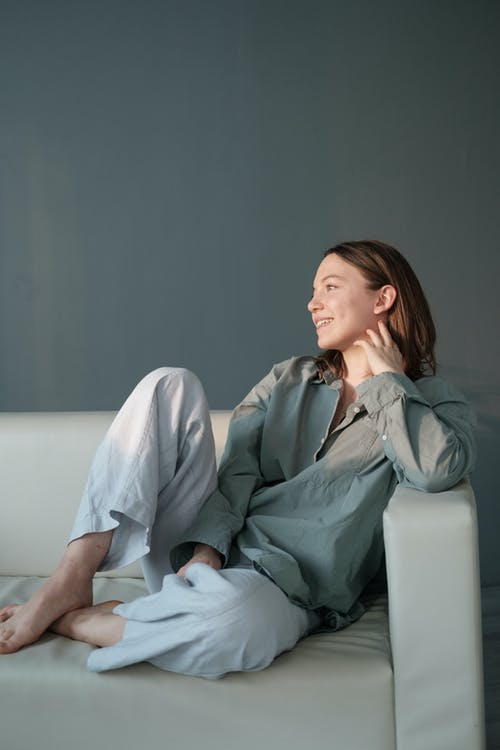 Smiling woman sitting on couch with legs crossed