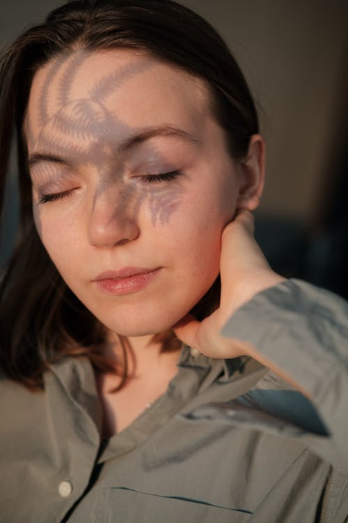 Serene woman with closed eyes and shadow from plant touching neck in bright sunshine