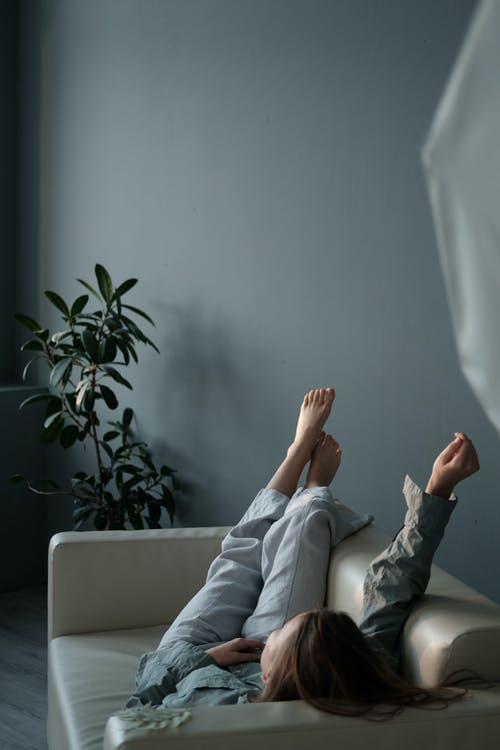 Full body of barefoot female with hand up chilling on couch placed near potted plant