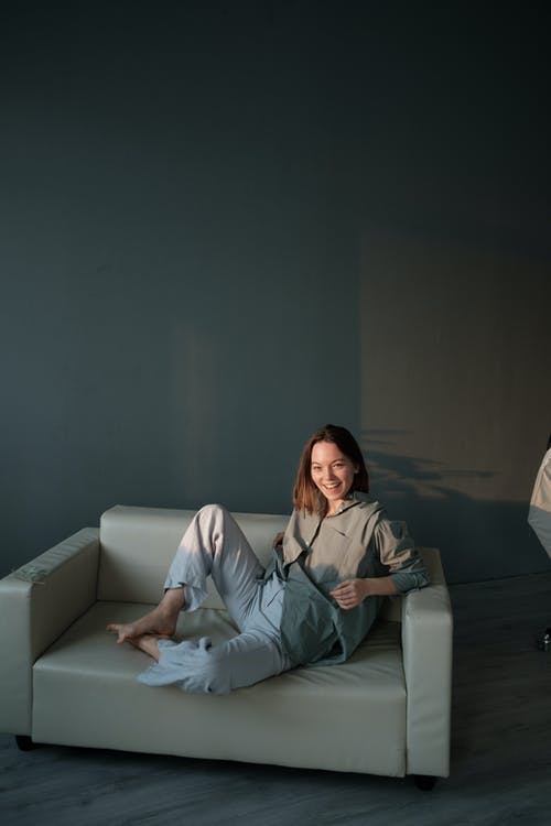 Positive woman resting on sofa in flat