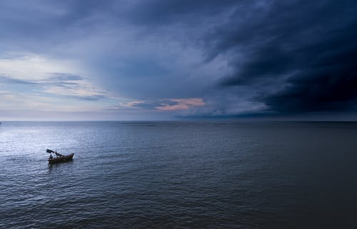 Silhouette of Boat on Sea Under Blue Sky