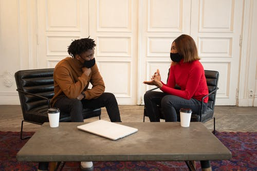 Focused African American colleagues in protective masks looking at each other while having conversation about work at table with laptop and paper cups of takeaway coffee