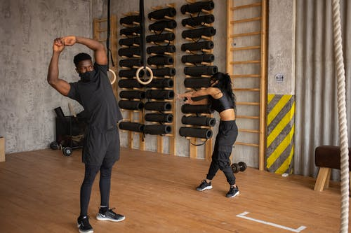 Black couple in face masks doing exercises