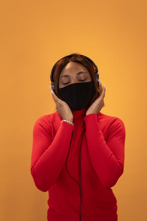 Calm African American female with closed eyes wearing protective mask listening to music in headphones on yellow background in studio