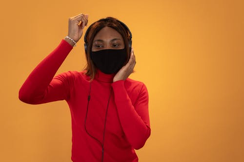 Content African American female wearing black protective mask listening to favorite music in headphones on yellow background in light studio