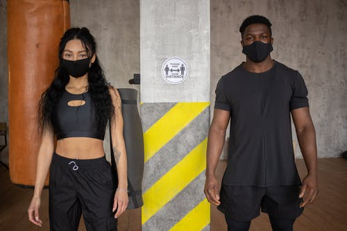 Young diverse female and African American male in protective masks standing at distance and looking at camera