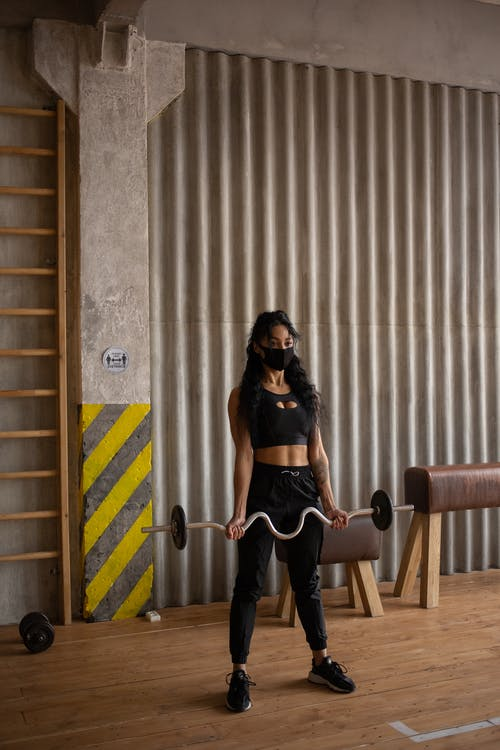 Young ethnic female in sportswear and protective mask lifting heavy barbell while training in gym