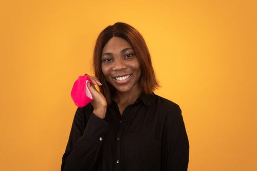 Happy Black woman with pink mask