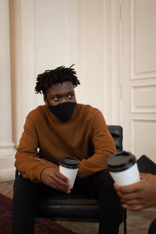 Black man in protective mask with coffee talking with friend