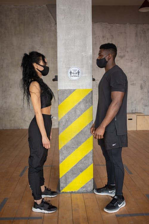 Full body side view female and African American male in protective masks standing at distance and looking at each other