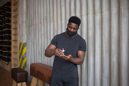 Black man applying antiseptic on palms