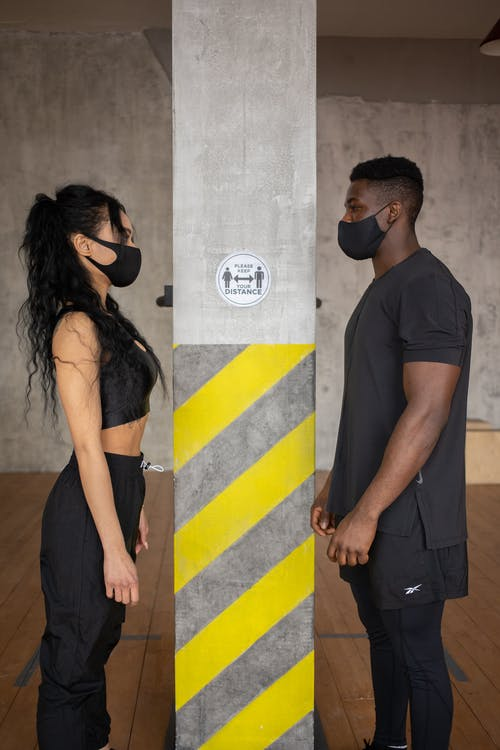 Side view of woman and black male in medical masks standing at distance and looking at each other