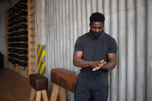Black man rubbing palms after applying antiseptic