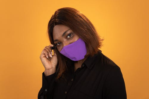 Female in purple medical mask against yellow background