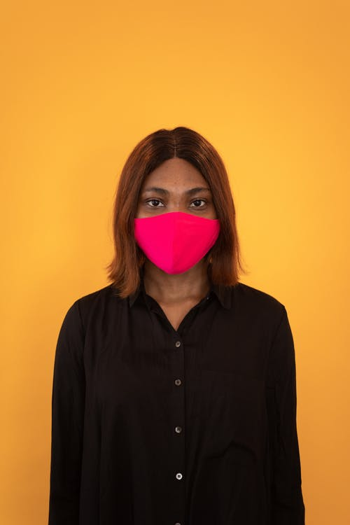 Isolated black woman in red protective mask looking at camera on yellow background