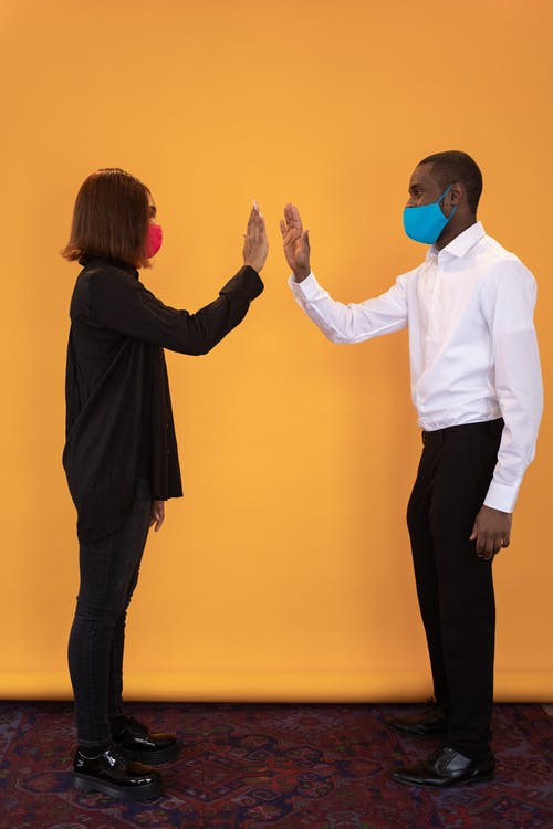 Full body of side view black friends in colorful medical masks joining hands at distance on yellow background