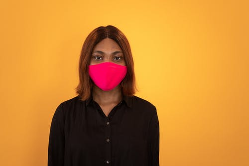 Young calm African American female in black blouse and face mask looking at camera against brown background