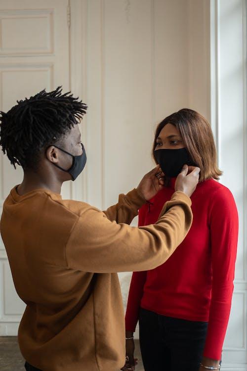 Black man putting face mask on girlfriend