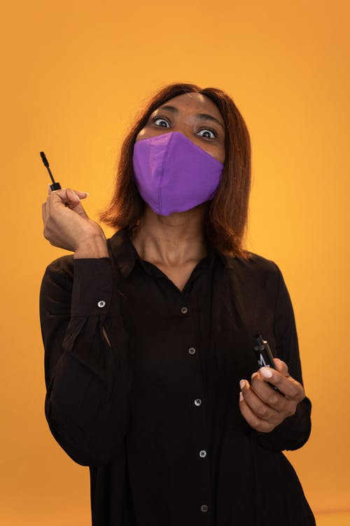Surprise black woman with mascara standing on brown background