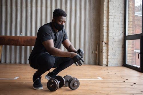 Black sportsman in mask hunkering down near dumbbells in gym