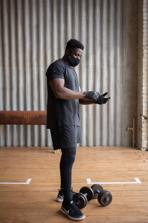 Black sportsman in mask putting on gloves in gym