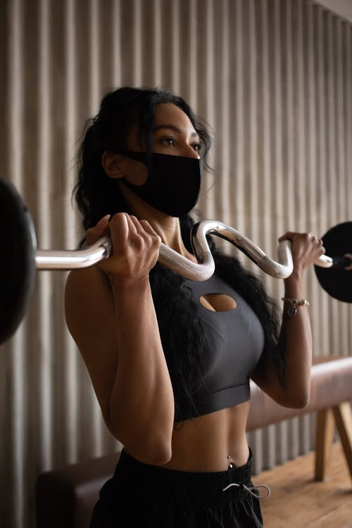Young sporty female in activewear and face mask exercising with barbell in gym