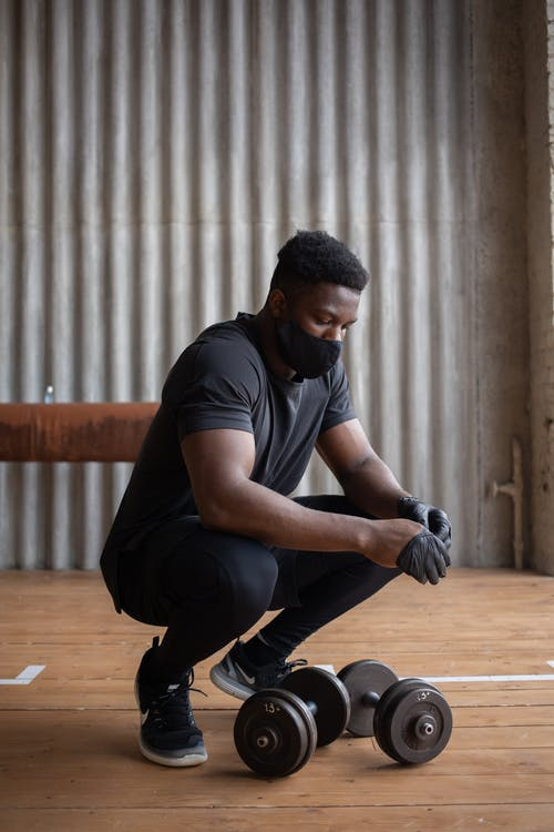 Full length focused African American sportsman in activewear and mask putting on latex gloves while hunkering down near dumbbells in gym