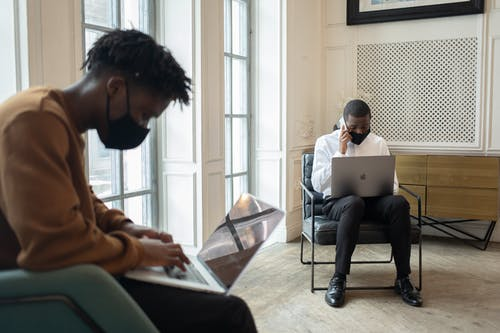 Black men in masks working on laptops in light room