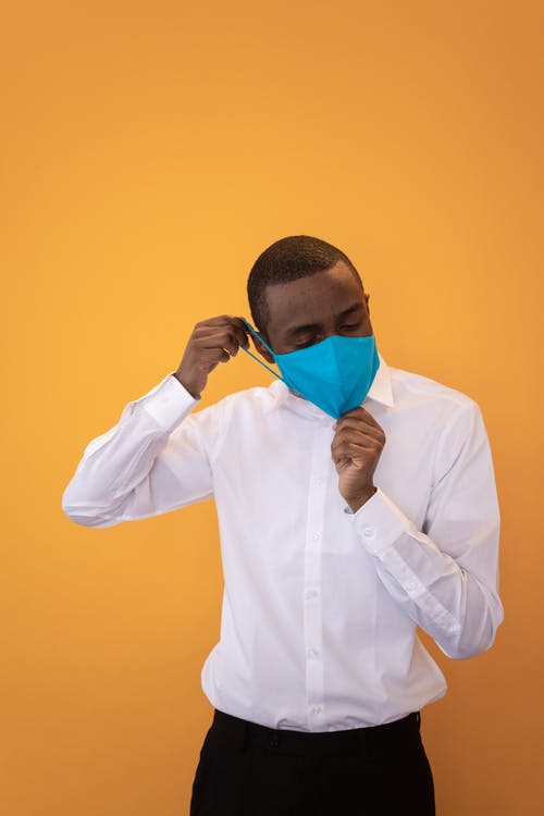African American male in formal clothes putting on protective mask in studio against yellow background
