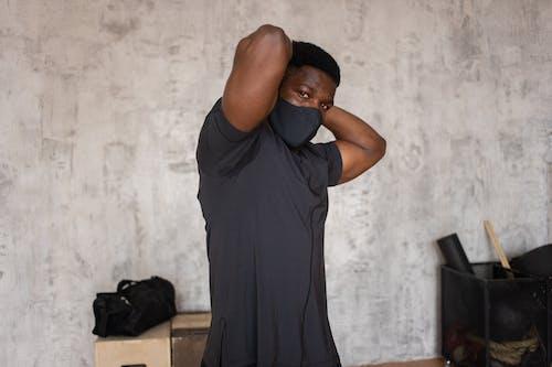 Man in Black Crew Neck T-shirt Standing Near White Wall