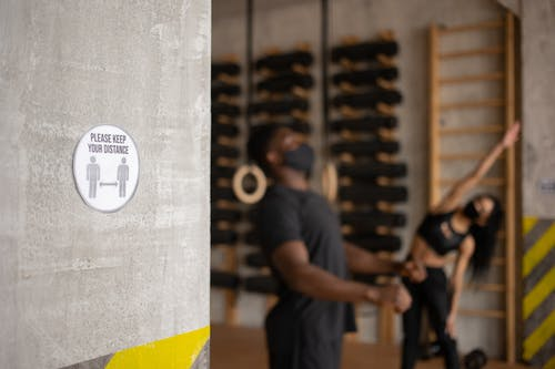 Distance sign in gym with unrecognizable black sportspeople during workout