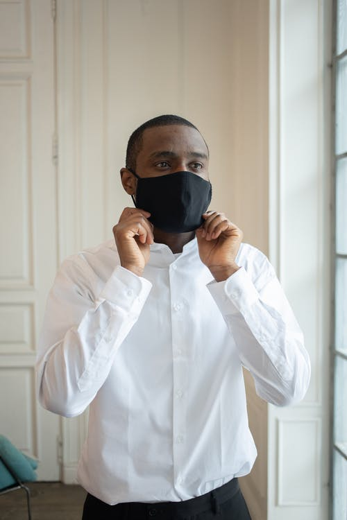 Reflective adult black male executive in white shirt putting on cloth face mask while looking away during COVID 19 pandemic indoors
