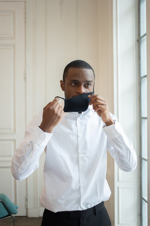 Adult ethnic male entrepreneur in white shirt taking off fabric mask while looking away during coronavirus pandemic in building