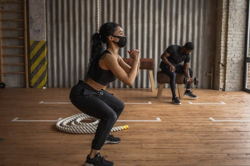 African American female athlete and unrecognizable sportsman in fabric masks exercising on floor in gymnasium