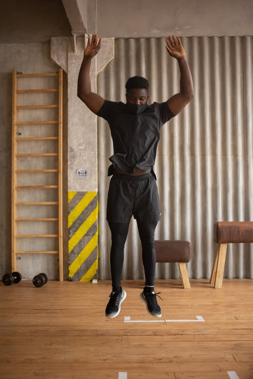 Man in Black T-shirt and Black Pants Doing Exercise