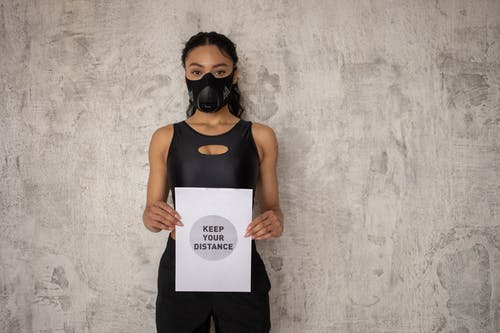 Black sportswoman in respiratory mask showing paper with inscription