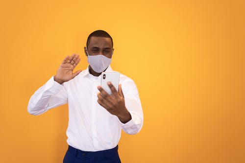 African American male entrepreneur in formal wear and cloth face mask waving hand during video call on cellphone on yellow background