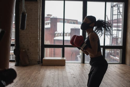 Woman Wearing Boxing Gloves and Face Mask