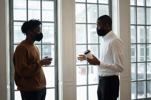 Side view of ethnic male director in fabric mask with coffee to go talking to employee while looking at each other indoors