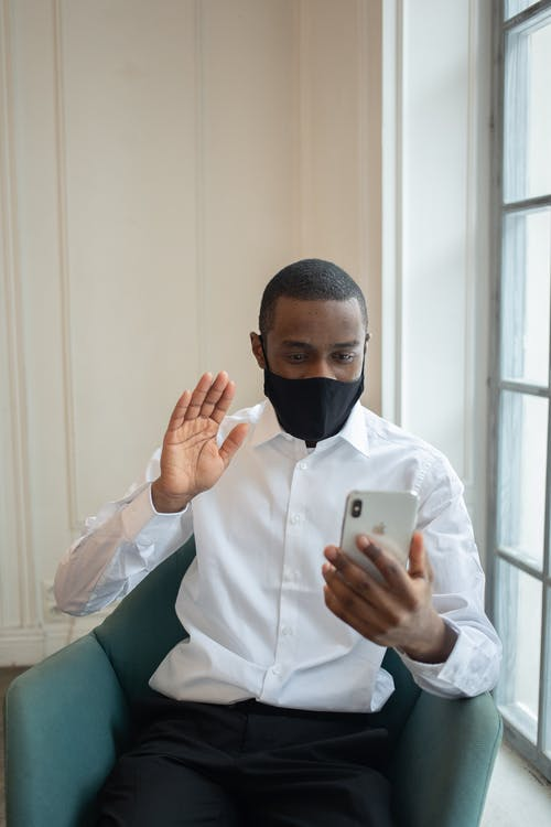 Black male executive in textile mask sitting in armchair while showing hello gesture during video chat on cellphone in workspace