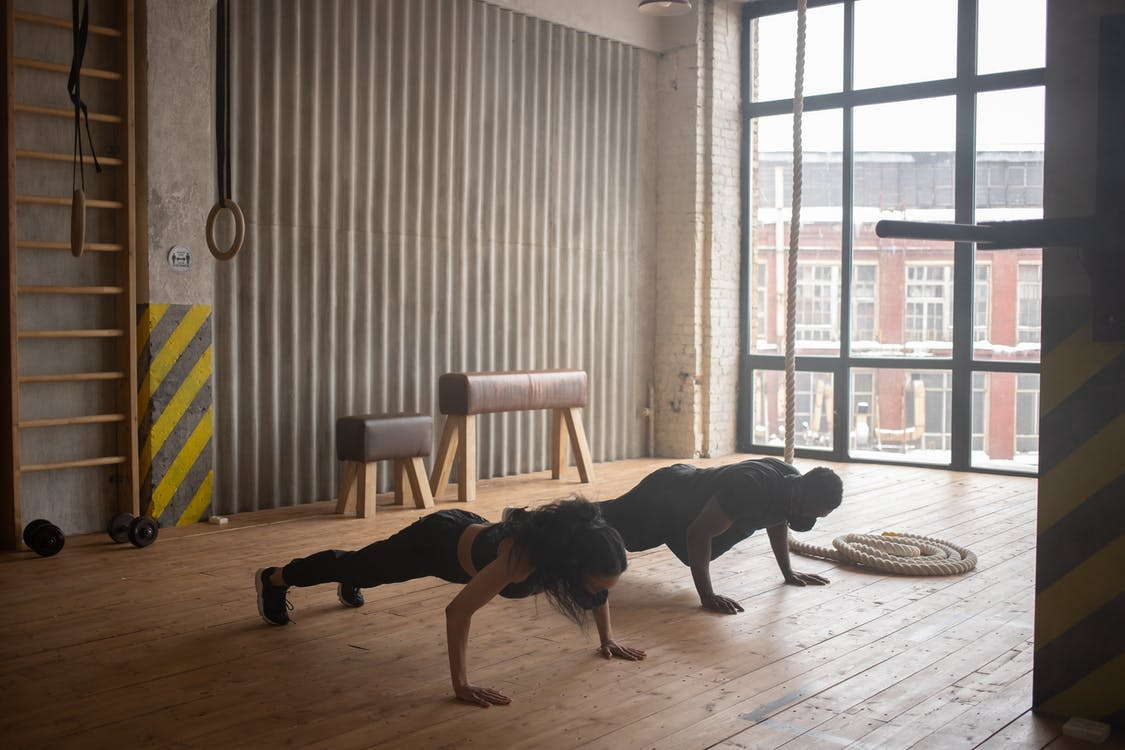 Unrecognizable black athletes in sportswear and cloth face masks standing in plank pose on floor in gym