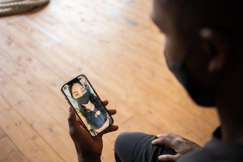 Crop black man talking to girlfriend in mask on smartphone