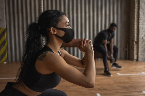 Tattooed black sportswoman in textile mask squatting against male partner with dumbbell during workout in gymnasium