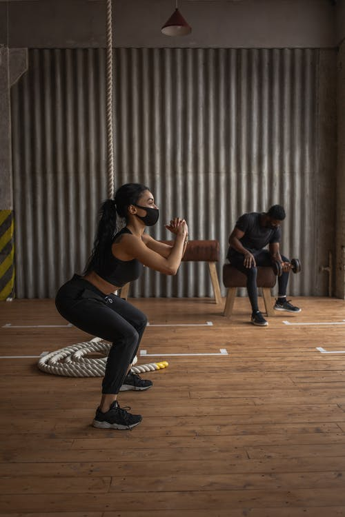 Black sportswoman in fabric mask squatting on floor against anonymous male athlete with dumbbell during training in gymnasium